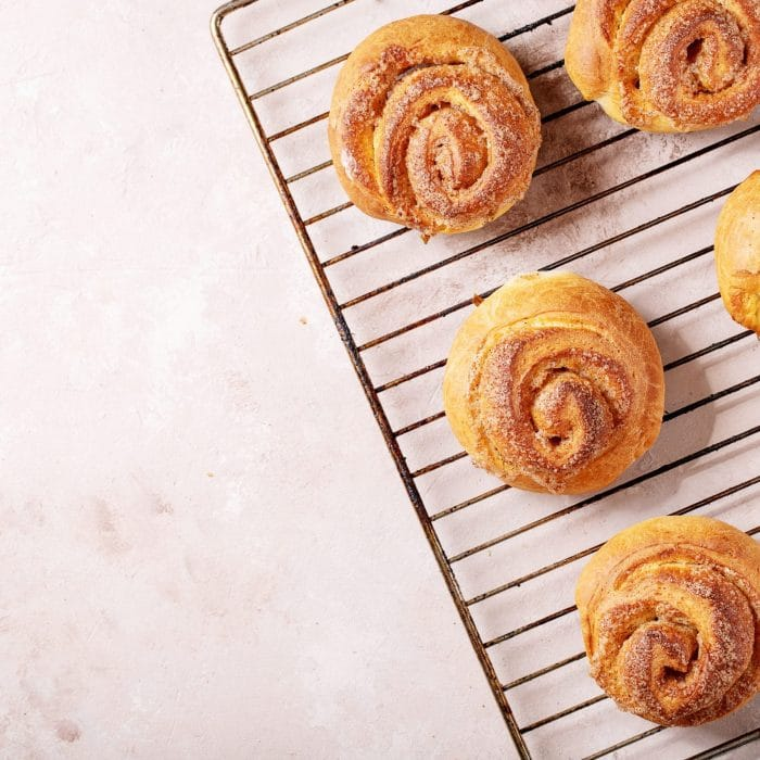 Baked cinnamon buns served with cinnamon and coffee over white texture background. Top view, flat lay. Copy space